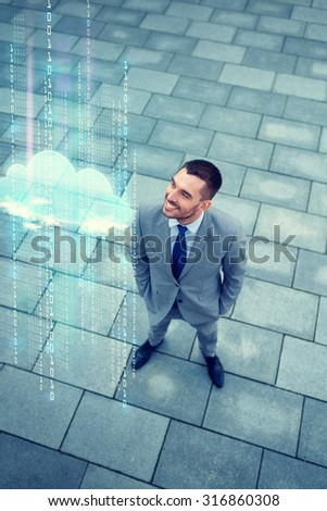 business, technology, progress, computing and people concept - young smiling businessman with cloud and binary code hologram outdoors from top - stock photo