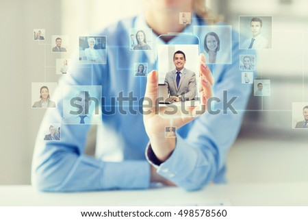 business, technology, social network, head hunting and people concept - close up of woman hand holding and showing transparent smartphone with contact icons on screen at office