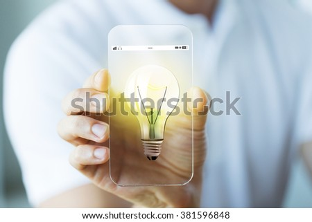 business, technology, startup, idea and people concept - close up of male hand holding and showing transparent smartphone with light bulb icon - stock photo