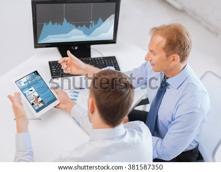 business, technology, statistics, economics and people concept - businessmen with charts on tablet pc and computer at office - stock photo