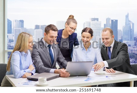 business, technology, teamwork and people concept - smiling business team with laptop computers, documents and coffee having discussion over office background - stock photo