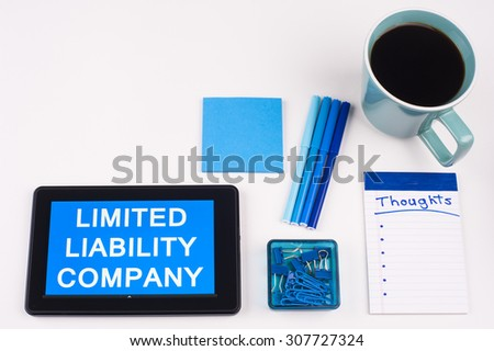 Business Term / Business Phrase on Tablet PC - Blue Colors, Coffee, Pens, Paper Clips and note pads on White - White Word(s) on blue - Limited Liability Company - stock photo