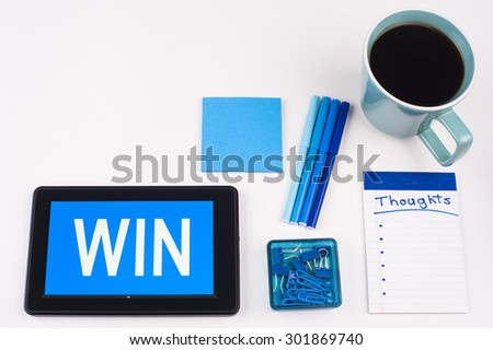 Business Term / Business Phrase on Tablet PC - Blues, cup of coffee, Pens, paper clips Calculator with a blue note pad on a White Background - White Word(s) on a blue background - Win