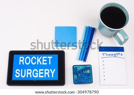 Business Term / Business Phrase on Tablet PC - Blues, cup of coffee, Pens, paper clips Calculator with a blue note pad on White - White Word(s) on blue - Rocket Surgery - stock photo