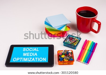 Business Term / Business Phrase on Tablet PC - Colorful Rainbow Colors, Cup, Notepad, Pens, Paper Clips, White surface - White Word(s) on a cyan background - Social Media Optimization - stock photo