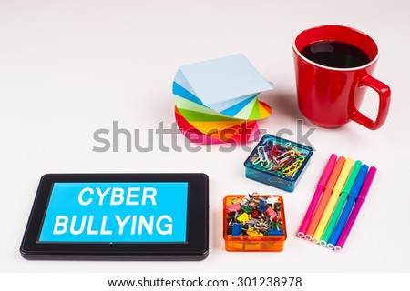 Business Term / Business Phrase on Tablet PC - Colorful Rainbow Colors, Cup, Notepad, Pens, Paper Clips, White surface - White Word(s) on a cyan background - Cyber Bullying - stock photo