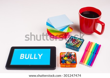 Business Term / Business Phrase on Tablet PC - Colorful Rainbow Colors, Cup, Notepad, Pens, Paper Clips, White surface - White Word(s) on a cyan background - Bully - stock photo