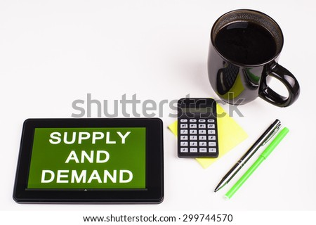 Business Term / Business Phrase on Tablet PC - Cup of coffee, Pens, Calculator and a green/yellow note pad on a White surface - White Word(s) on a green background - Supply And Demand - stock photo