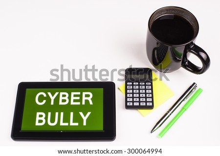 Business Term / Business Phrase on Tablet PC - Cup of coffee, Pens, Calculator and a green/yellow note pad on a White surface - White Word(s) on a green background - Cyber Bully - stock photo
