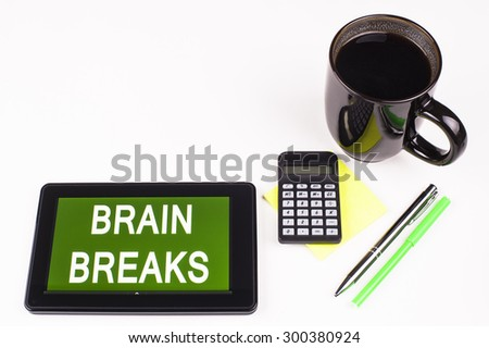 Business Term / Business Phrase on Tablet PC - Cup of coffee, Pens, Calculator and a green/yellow note pad on a White surface - White Word(s) on a green background - Brain Breaks - stock photo