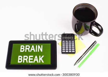 Business Term / Business Phrase on Tablet PC - Cup of coffee, Pens, Calculator and a green/yellow note pad on a White surface - White Word(s) on a green background - Brain Break - stock photo