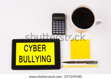 Business Term / Business Phrase on Tablet PC with a cup of coffee, Pens, Calculator, and yellow note pad on a White Background - Black Word(s) on a yellow background - Cyber Bullying - stock photo