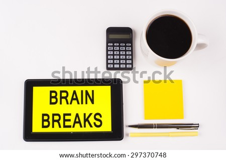 Business Term / Business Phrase on Tablet PC with a cup of coffee, Pens, Calculator, and yellow note pad on a White Background - Black Word(s) on a yellow background - Brain Breaks - stock photo