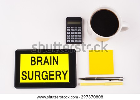 Business Term / Business Phrase on Tablet PC with a cup of coffee, Pens, Calculator, and yellow note pad on a White Background - Black Word(s) on a yellow background - Brain Surgery - stock photo