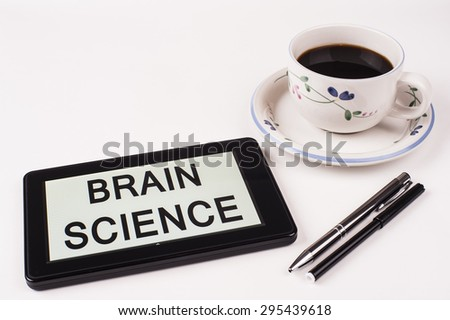 Business Term / Phrase on Tablet PC with a cup of coffee and pens on a White Background - Black Word(s) on a white background - Brain Science - stock photo