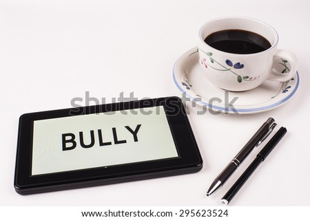 Business Term / Phrase on Tablet PC with a cup of coffee and pens on a White Background - Black Word(s) on a white background - Bully - stock photo