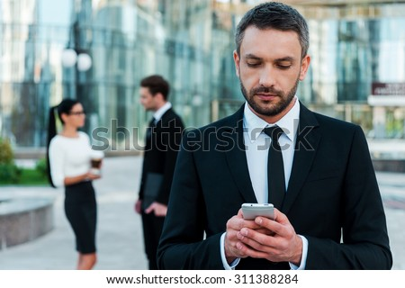 Business texting. Serious young businessman holding mobile phone and looking at it while two his colleagues talking to each other in the background - stock photo