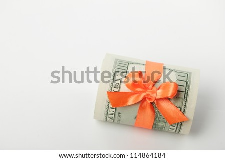 Business theme as dollars with orange ribbon over light gray background - stock photo