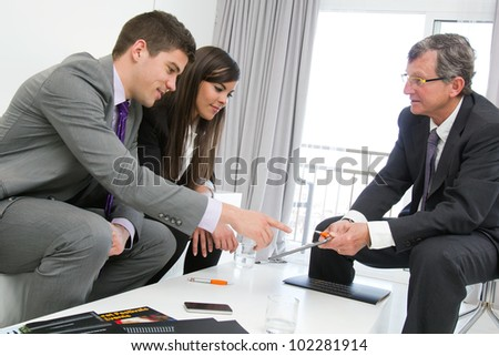 Business threesome at financial meeting with documents and tablet on table.