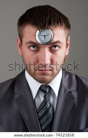 Business time - businessman looking to clock in head - stock photo
