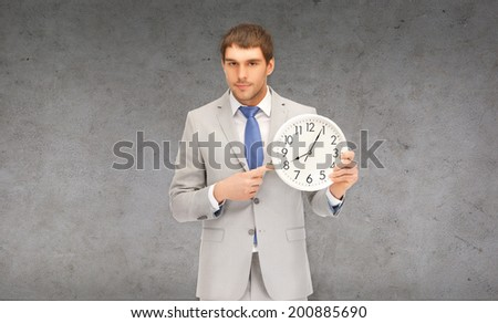 business, time magement and office concept - handsome businessman pointing finger to wall clock - stock photo