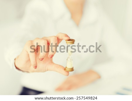 business, time management, deadline concept - woman hand with sandglass - stock photo