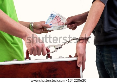 Business transfer deal. exchange between money and suitcase caught by hand with handcuffs - stock photo