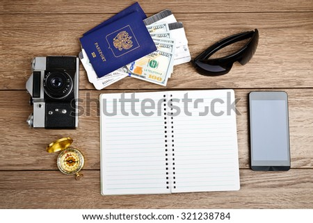 Business travel and tourism concept: air tickets or boarding pass, passports, smartphone, compass, vintage camera, sunglasses - stock photo