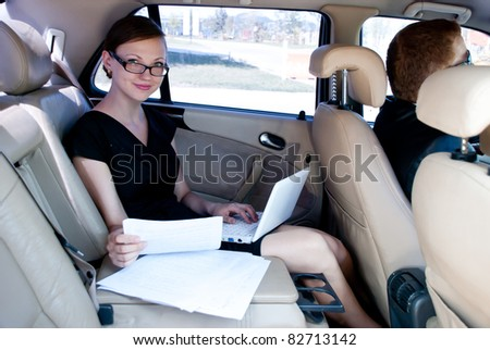 business travel: busy businesswoman with document and laptop in car - stock photo