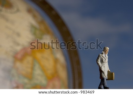 Business travel figure in front of globe with clouds in background - stock photo