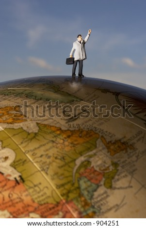 Business travel figure on globe with clouds in background - stock photo