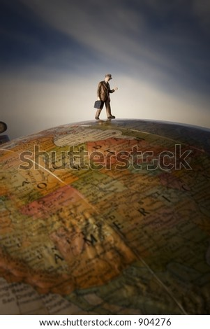 Business travel figure on globe with clouds in background and spotlight on figure - stock photo