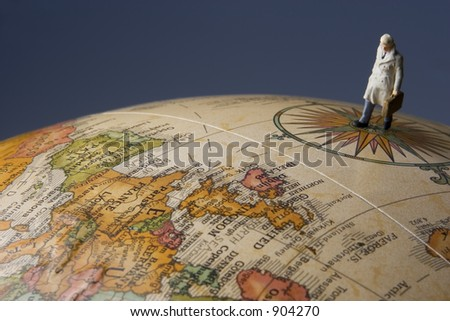 Business travel figure on globe with dark blue background - stock photo