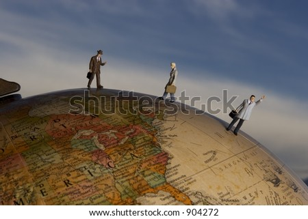 Business travel figures on globe with clouds in background - stock photo