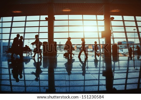 business travel, silhouettes of unrecognizable walking people in the airport - stock photo