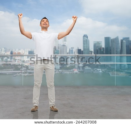 business, travel, tourism, gesture and people concept - happy man with raised hands over city background - stock photo
