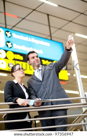 business travellers pointing at flight information board