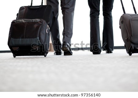 business travellers walking in airport with luggage - stock photo