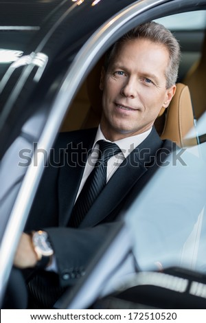 Business trip. Confident senior businessman sitting in car and smiling at camera - stock photo