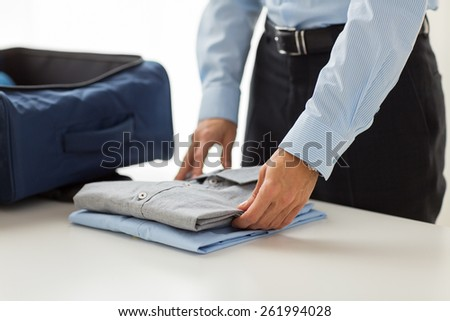 business, trip, luggage and people concept - close up of businessman packing clothes into travel bag - stock photo