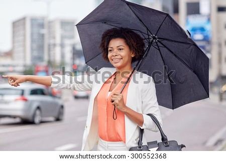 business trip, transportation and people concept - young smiling african american woman with umbrella catching taxi at city street - stock photo