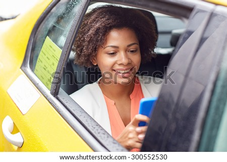 business trip, transportation, travel, gesture and people concept - young smiling african american woman texing on smartphone in taxi at city street - stock photo
