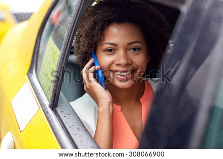 business trip, transportation, travel, gesture and people concept - young smiling african american woman calling on smartphone in taxi at city street - stock photo