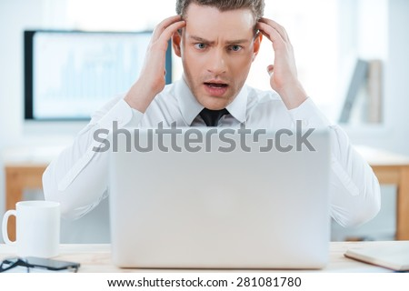 Business troubles. Frustrated businessman working on laptop and touching his head while sitting at his working place - stock photo