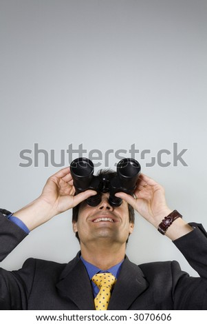 business vision: businessman looking up though binoculars - stock photo
