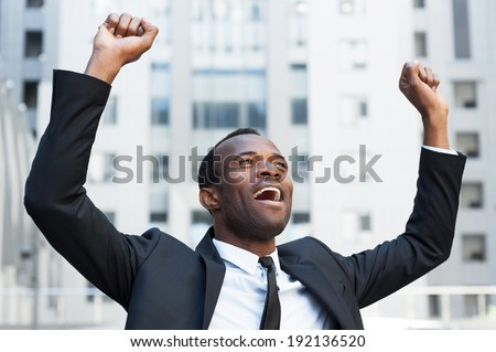 Business winner. Happy young African man in formal wear keeping arms raised and expressing positivity while standing outdoors - stock photo