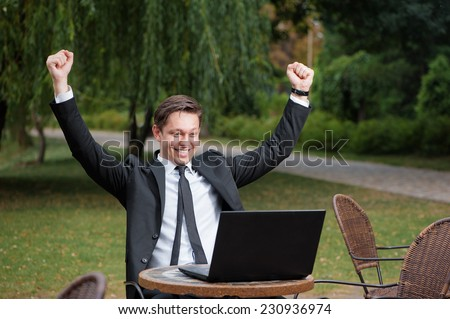 Business winner. Happy young caucasian man in formal wear keeping arms raised and expressing positivity while sitting a the  outdoors cafe working with laptop with park in the background - stock photo