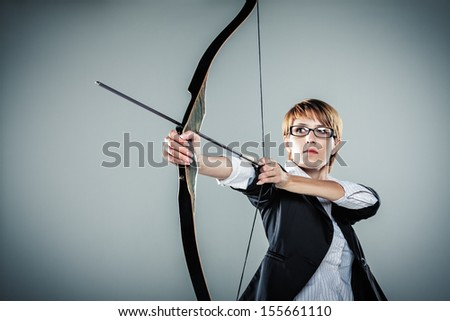 Business woman aiming with bow and arrow grey background - stock photo