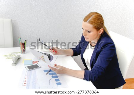 Business woman analyzing investment charts with calculator and laptop - stock photo