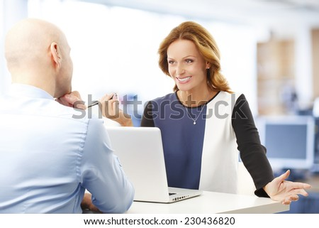 Business woman and businessman discussing problems, while sitting at office. Teamwork.  - stock photo
